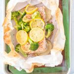 cooked salmon, lemon slices, and vegetables in parchment paper on a baking sheet