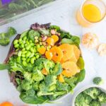 spinach salad with mandarin oranges in a large bowl with ingredients around it