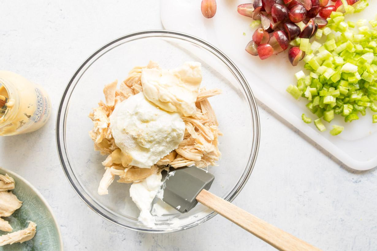 chicken, mayonnaise, and Greek yogurt in a glass bowl