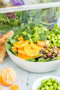 spinach salad with mandarin oranges in a bowl with ingredients around it