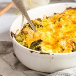 chicken broccoli divan in a white baking dish with a spoon in it