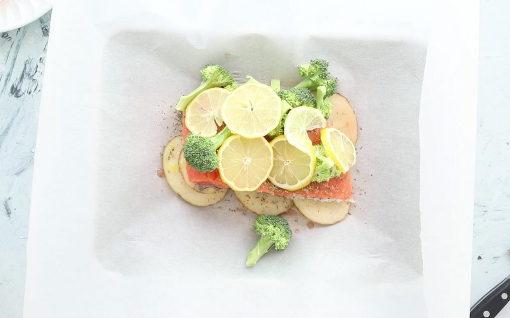 sliced potatoes with salmon then broccoli and lemons on top of parchment paper
