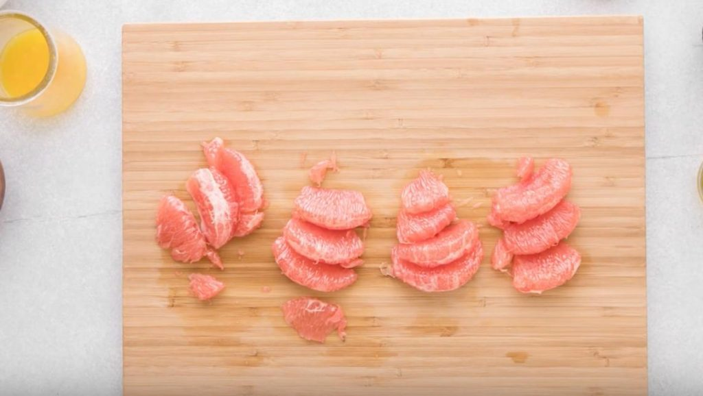 grapefruit sections on a wooden cutting board