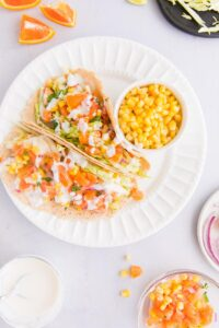 fish tacos with white sauce and orange salsa on a white plate