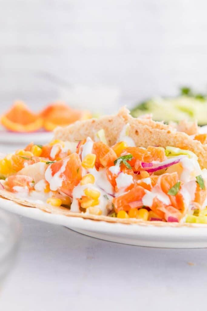 close up of fish tacos with white sauce and orange salsa on a plate