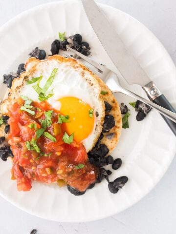 huevos rancheros with salsa on a white plate