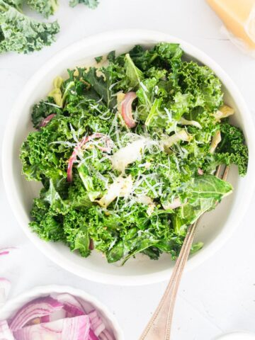 close up of warm kale salad in a white bowl with a fork in it