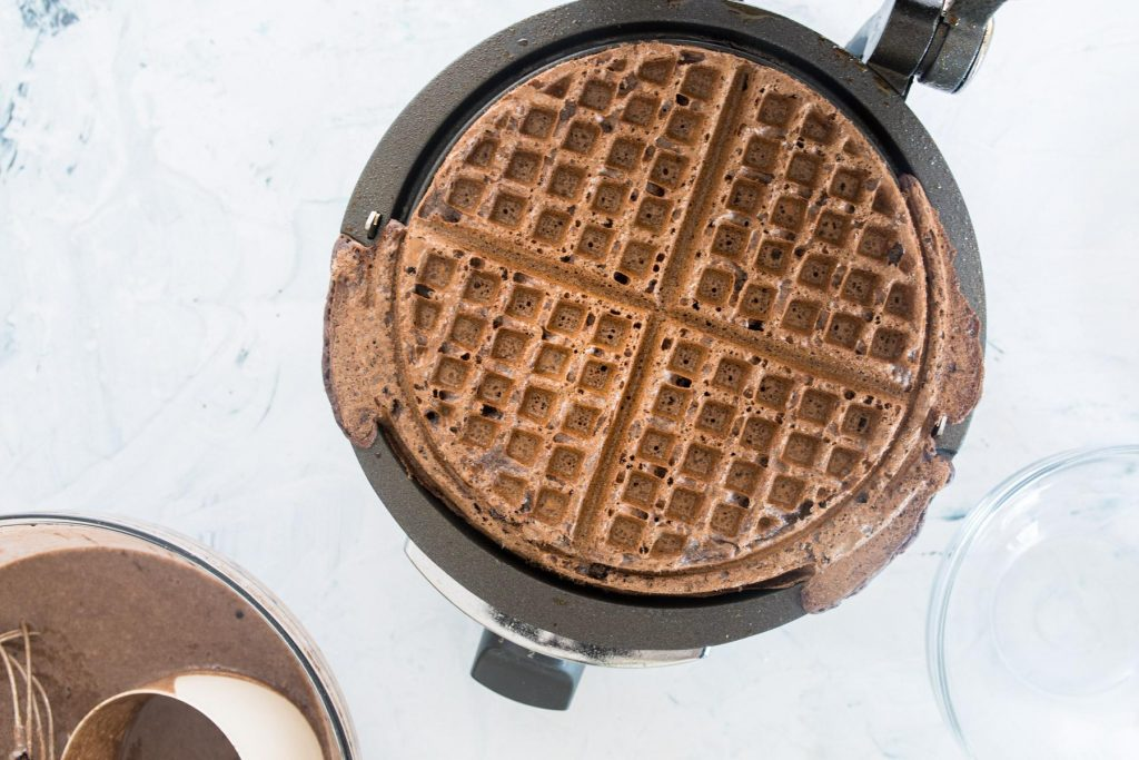 cooked dark chocolate waffle in a waffle iron