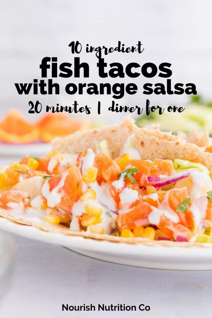 close up of fish tacos with white sauce and orange salsa on a plate with text overlay