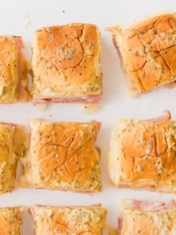 ham and swiss sliders on Hawaiian rolls on a table