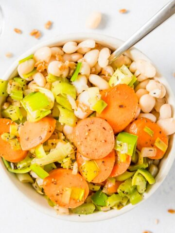 close up of carrots, leeks, and white beans in a bowl