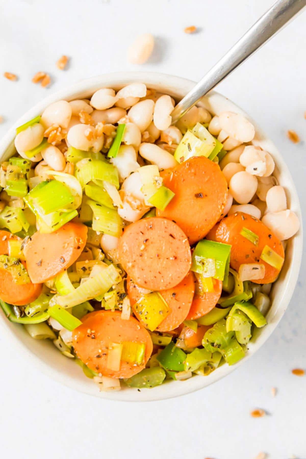 carrots, leeks, and white beans in a white bowl with a spoon in it