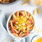 black bean pasta and cheese on top in a white bowl with ingredients around it.