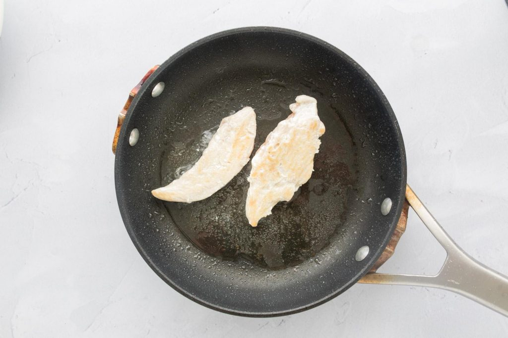 two chicken tenders in a small frying pan