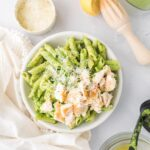 square image of pesto pasta with chicken and parmesan cheese