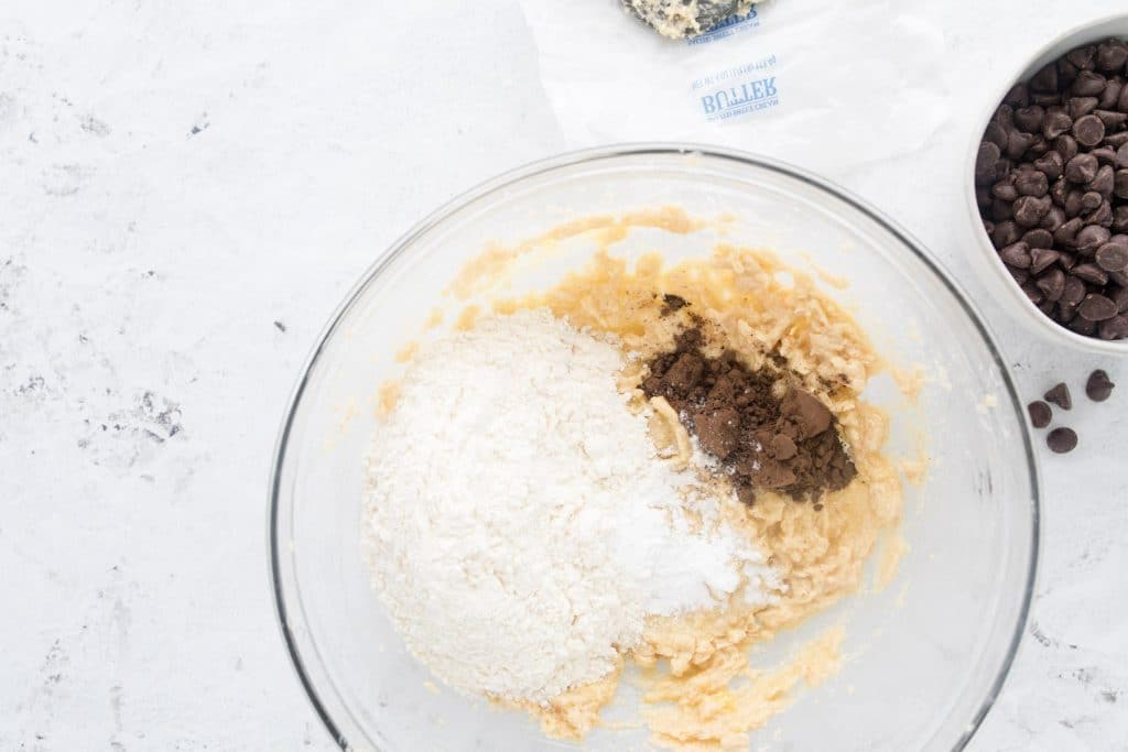 Flour, cocoa powder, and creamed butter and sugar in a glass bowl