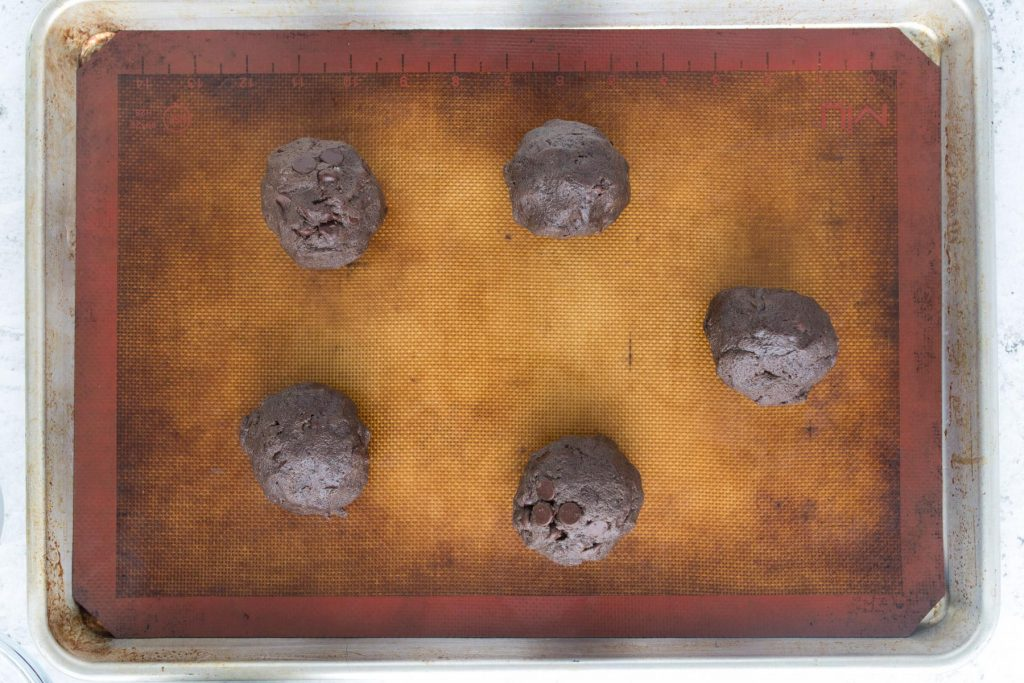 double chocolate cookie balls on a cookie sheet