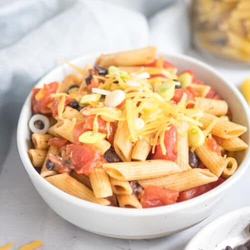 black bean pasta in a white bowl with ingredients around it