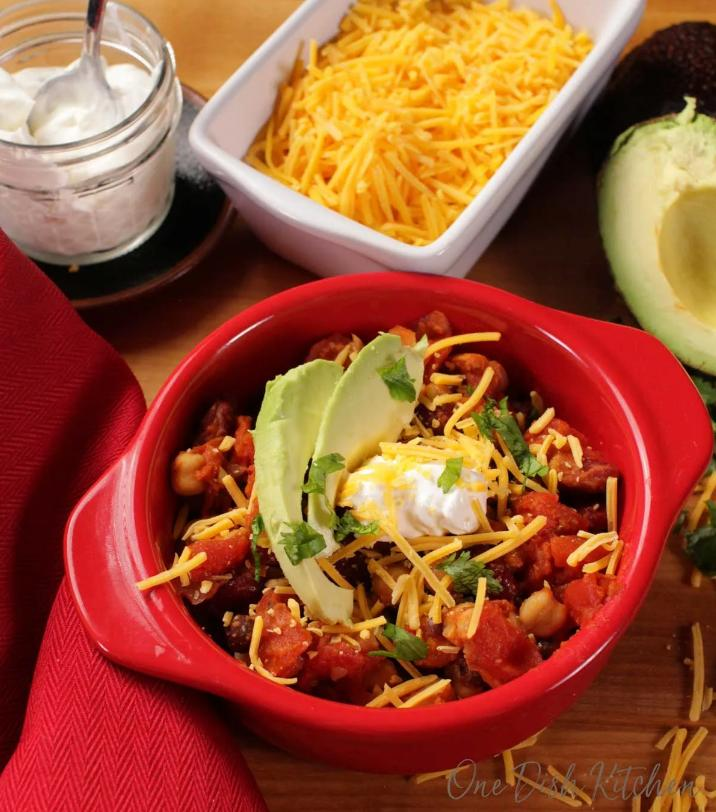 Vegetarian chili in a red bowl with cheese and avocado on top