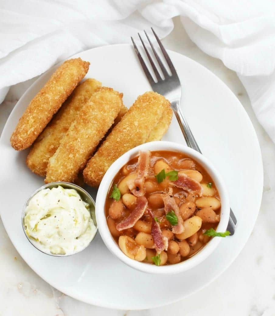 baked beans with bacon in a bowl with fish sticks on a plate
