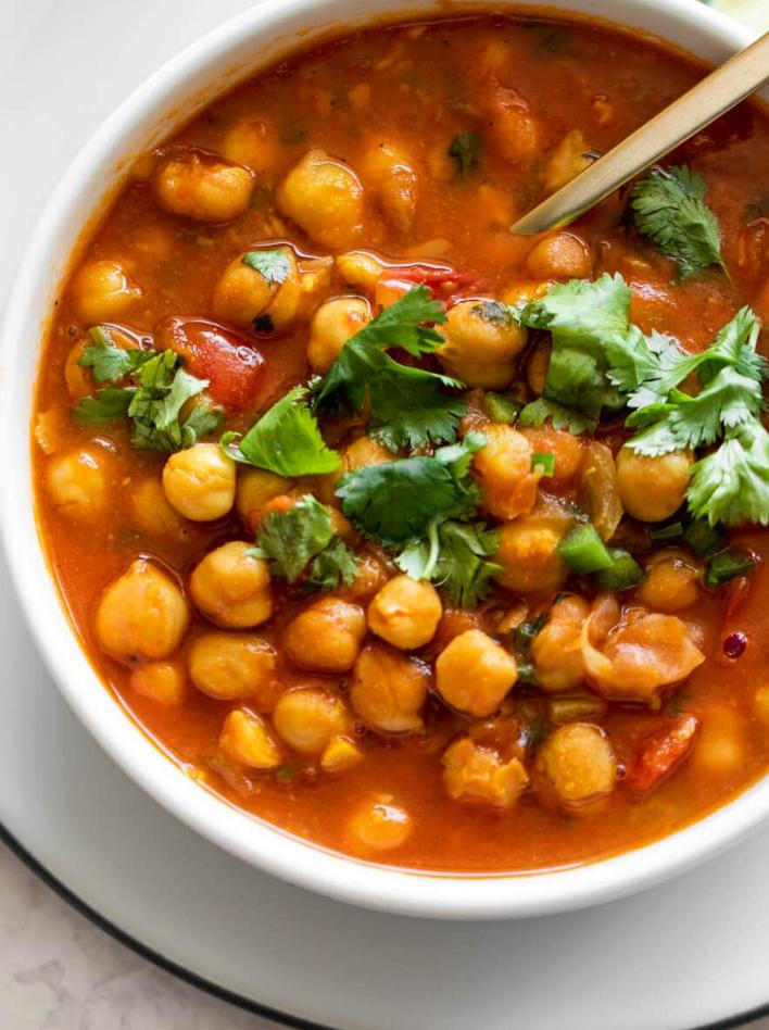 chana masala with cilantro on top in a white bowl