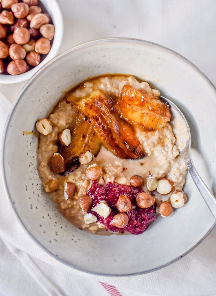 caramelized banana oatmeal in a bowl with hazelnuts next to it
