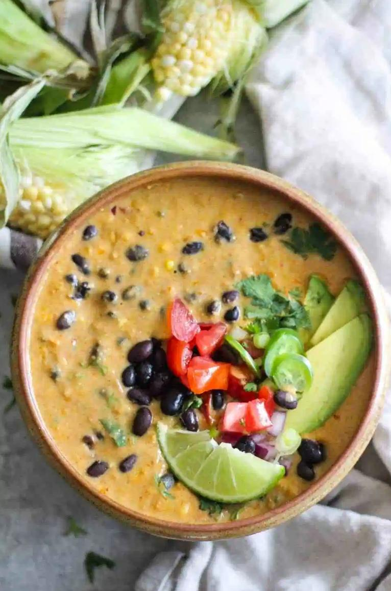 vegan corn chowder with tomatoes, black beans, a lime, and avocado on top