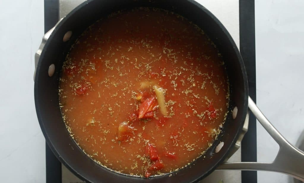 pasta, water, tomatoes, and spices in a black pot