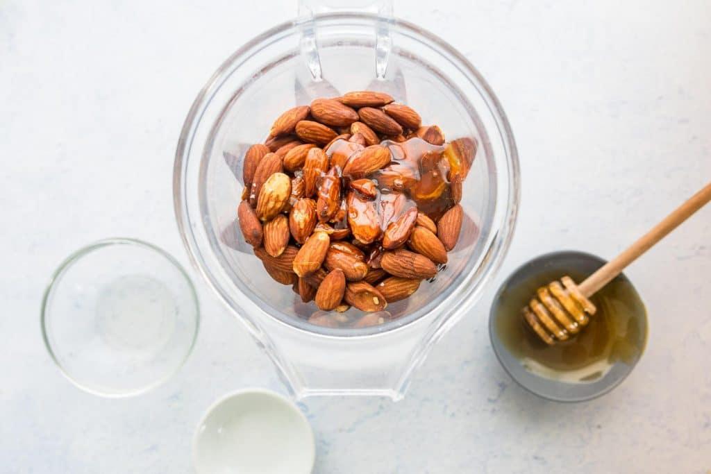 ingredients for honey almond butter in a blender jar