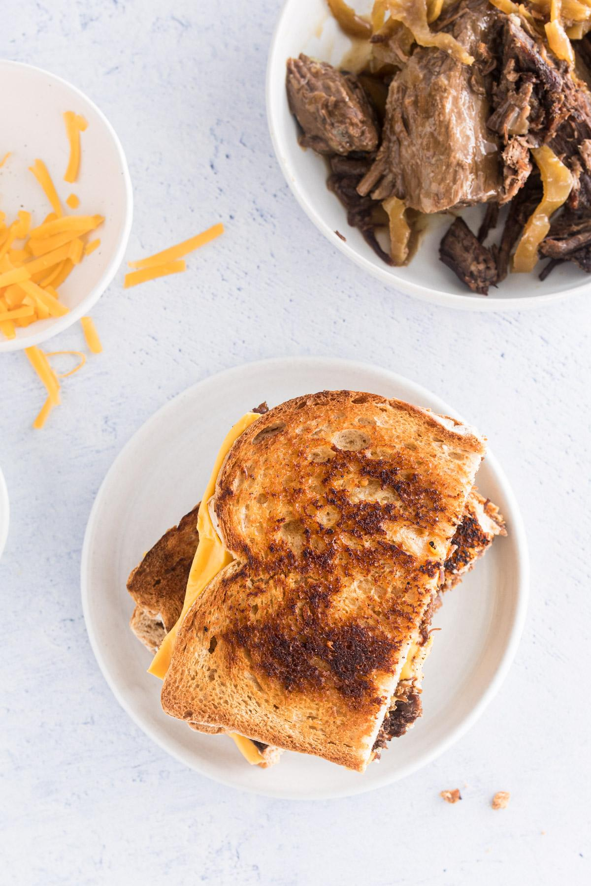 brisket grilled cheese on a plate next to brisket and cheese in bowls
