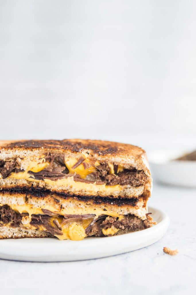 open slices of brisket grilled cheese on a plate