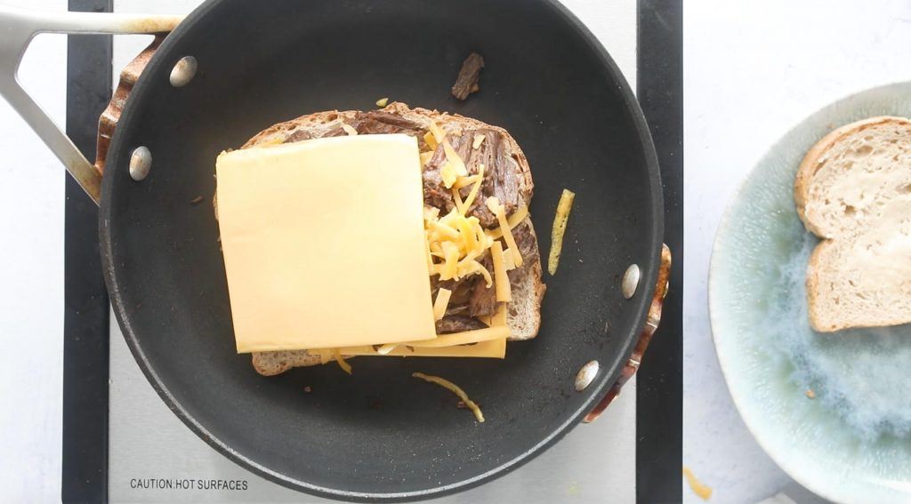 a slice of bread with cheese and brisket on it