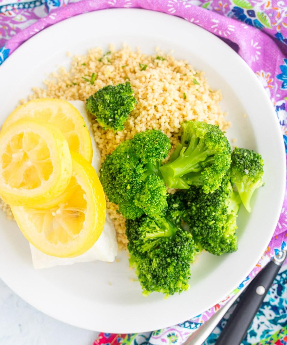 cod with lemon on top next to couscous and broccoli