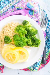 cod with lemon slices on top with couscous and broccoli on a white plate