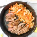 steak, peppers, and onions in a cast iron skillet surrounded by fajita ingredients