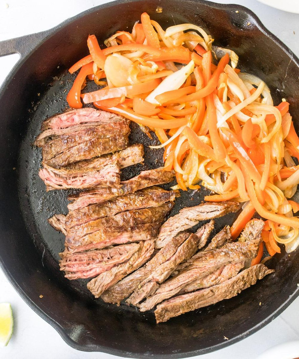 sliced steak, peppers and onions in a cast iron skillet
