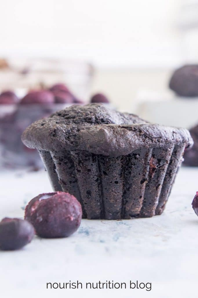 chocolate blueberry muffin standing on a table with blueberries surrounding it with text overlay