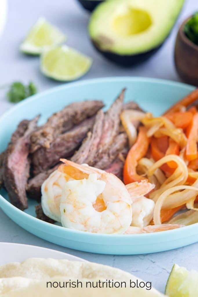 shrimp, steak, and vegetables in a blue bowl with other foods surrounding it