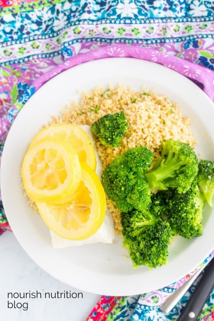 cod with lemon on top next to couscous and broccoli with text overlay