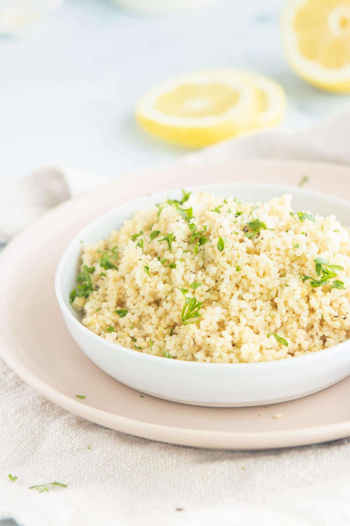 couscous on a pink plate with lemons in back