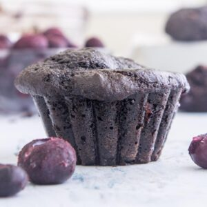 chocolate blueberry muffin standing on a table with blueberries surrounding it