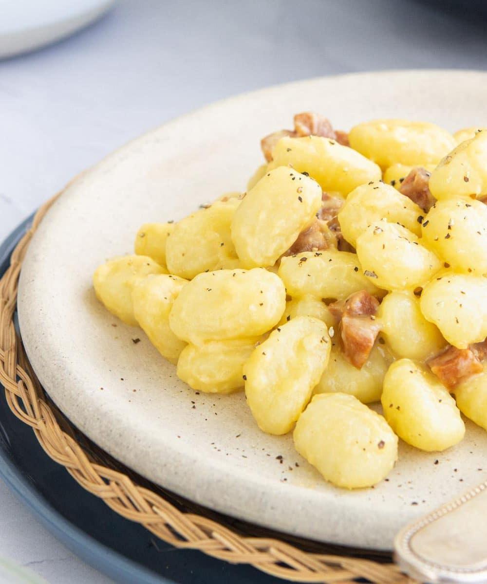 close up photo of gnocchi carbonara on a plate