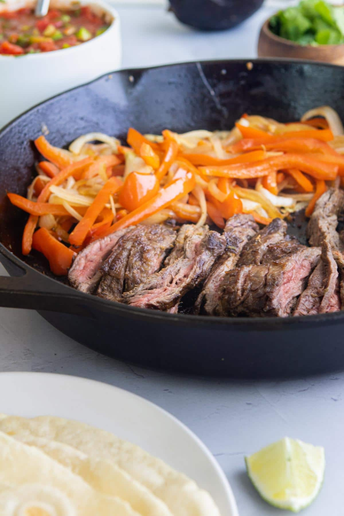 sliced steak, red bell peppers, and onions on a cast iron skillet