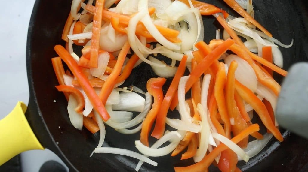 peppers and onions cooking on a cast iron skillet