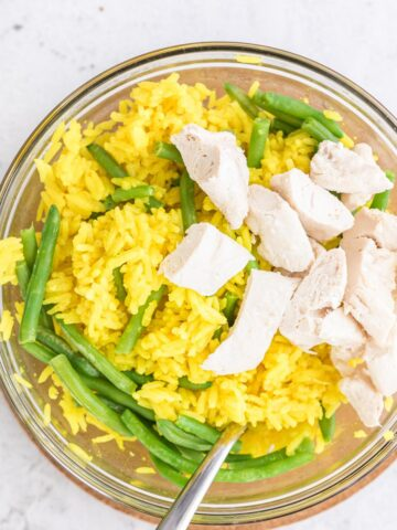 close up of chicken and yellow rice in a glass bowl