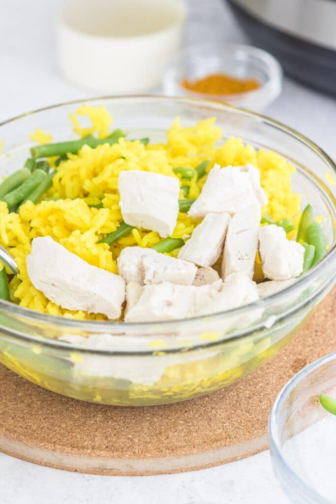 chicken and yellow rice in glass bowl