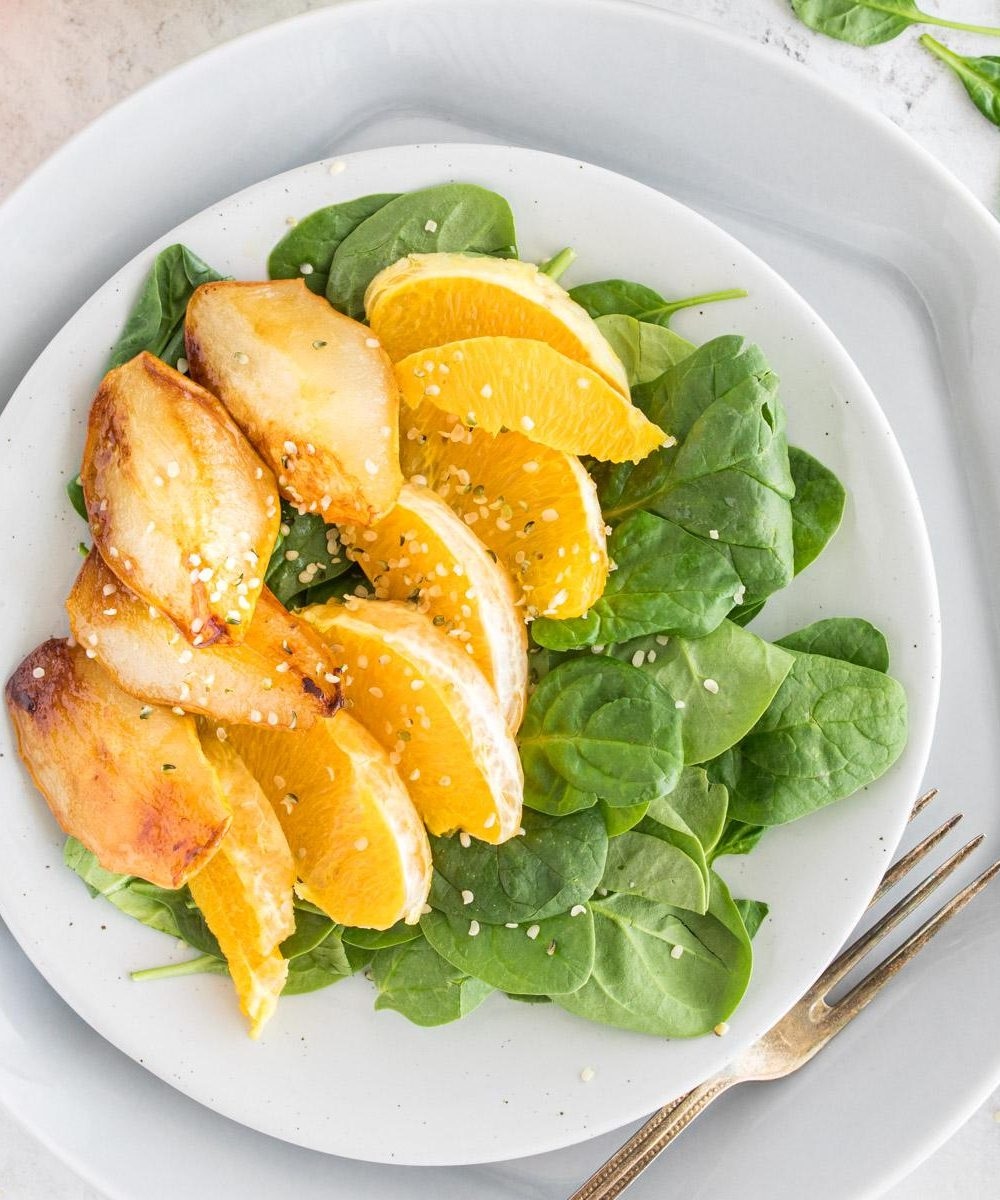 light blue plate with spinach, orange slices, and roasted pears on it