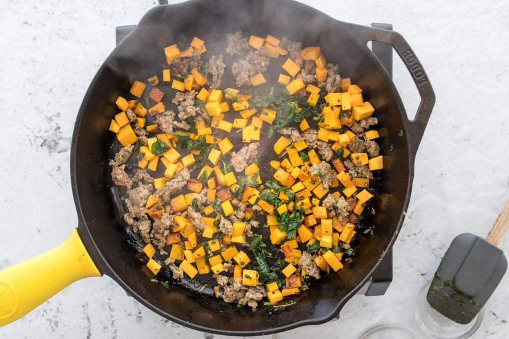 butternut squash, sausage, and spinach in skillet