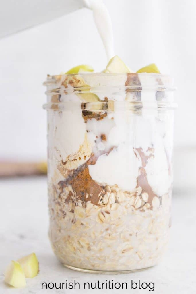 pouring milk into a glass jar of overnight oats with text overlay