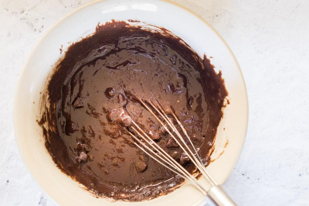 brownie batter in a mixing bowl with whisk in it